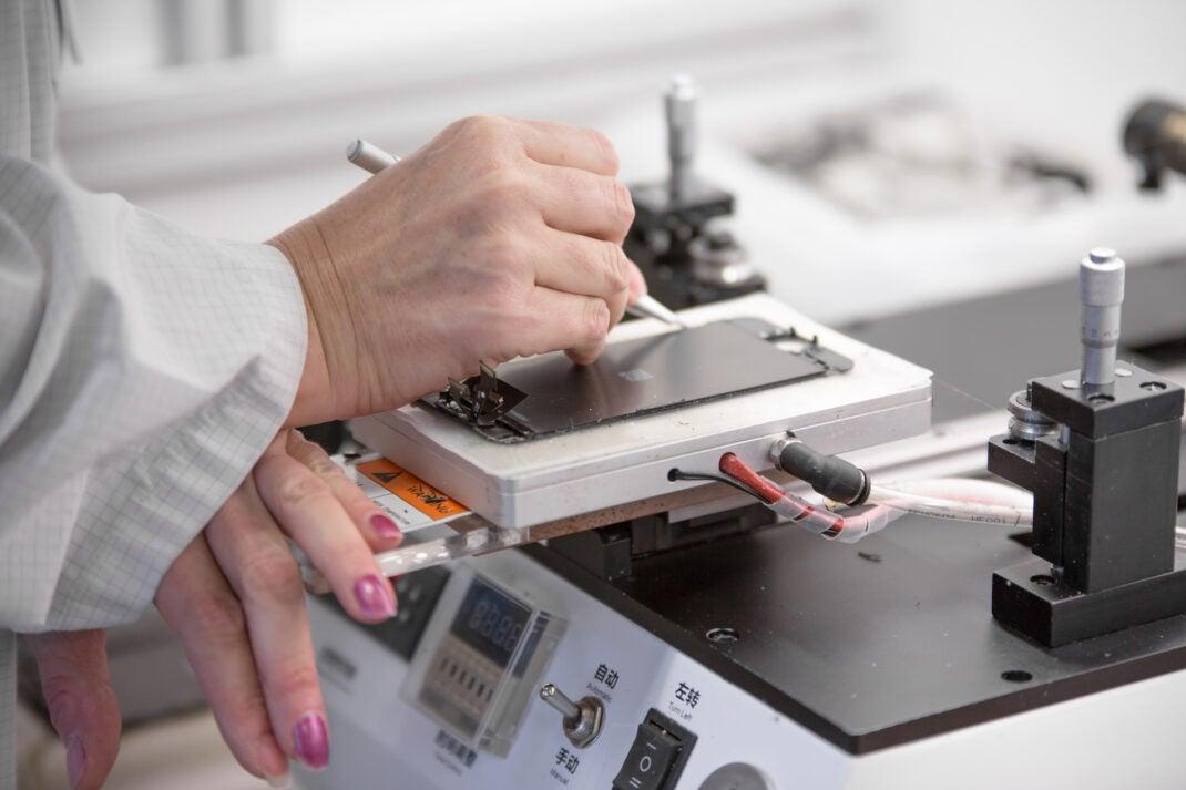 Frau beklebt repariert Smartphone