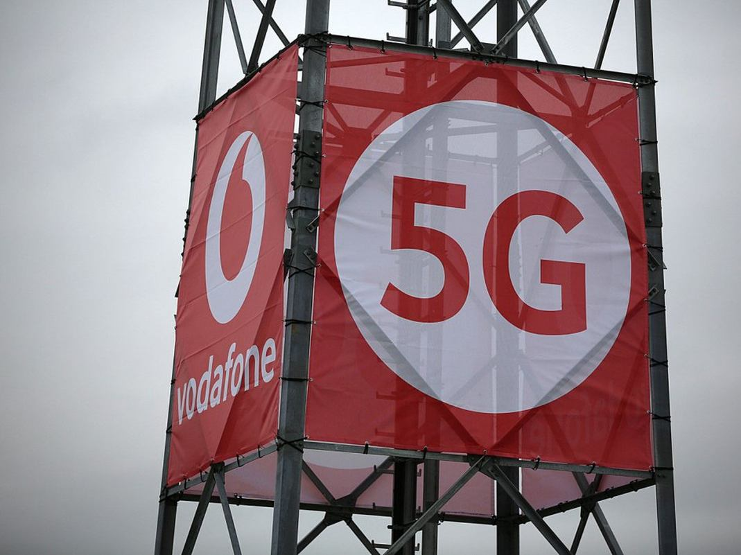 Ein 5G-Logo von Vodafone an einem Mast