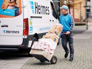 Ein Hermes Zusteller mit Paketen vor seinem Fahrzeug.