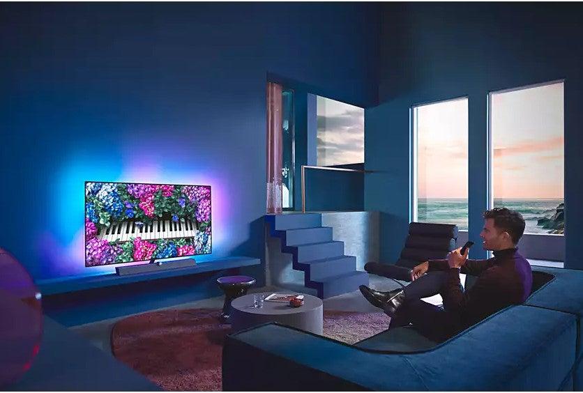 Ein Mann sitzt vor einem Fernseher, der nach außen hin leuchtet.