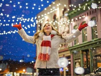 Frau steht an Weihnachten im Schnee