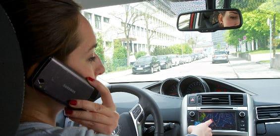 Autofahrerin nutzt Handy und Navi am Steuer