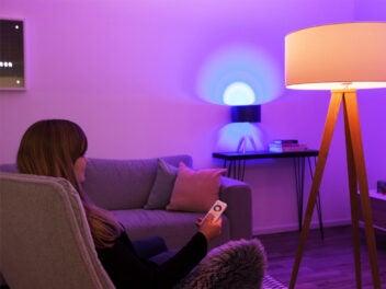Aldi tint: Frau sietzt im lila illuminierten Wohnzimmer