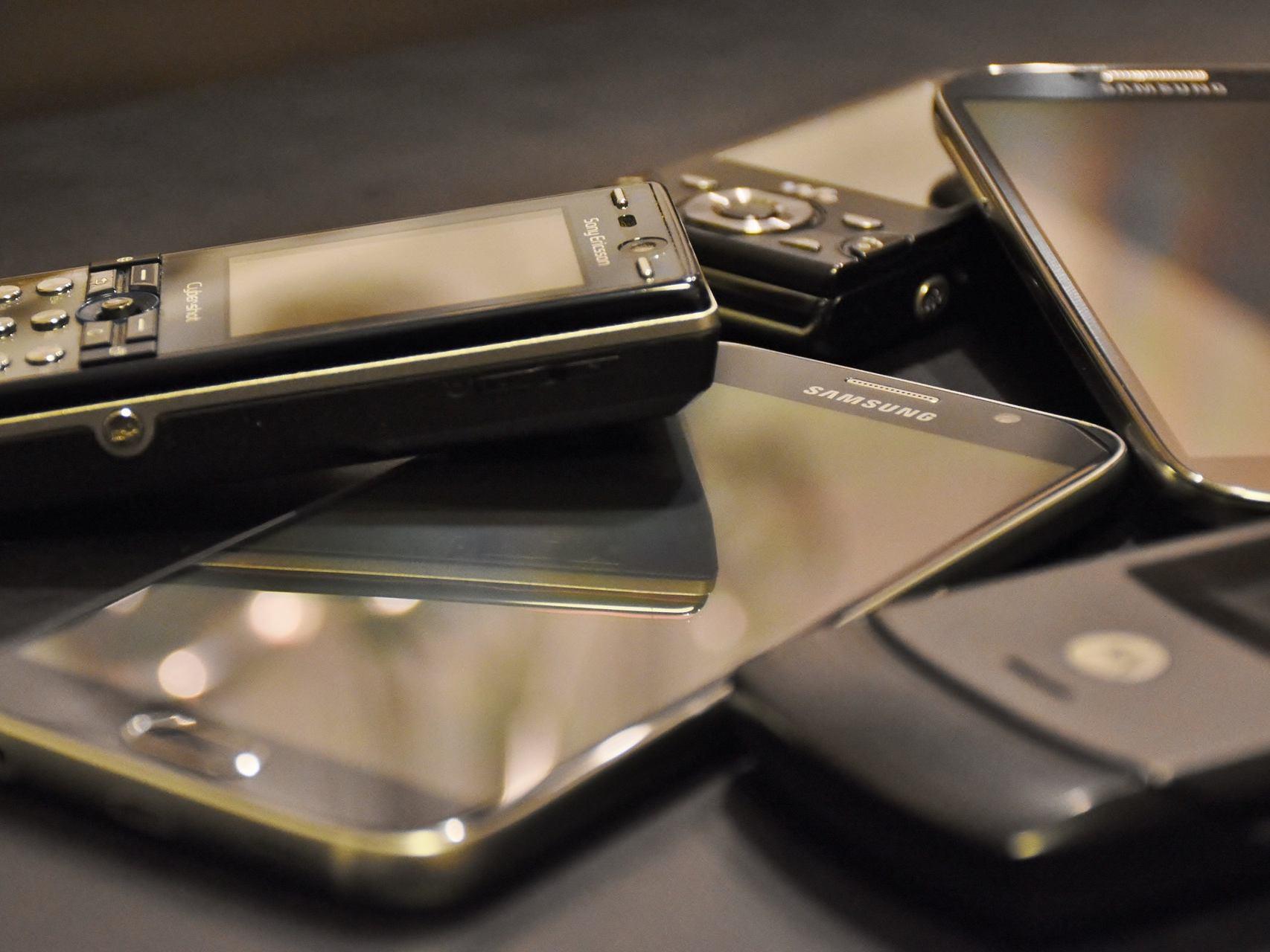 Einige alte Handys und Smartphones liegen auf einem Tisch