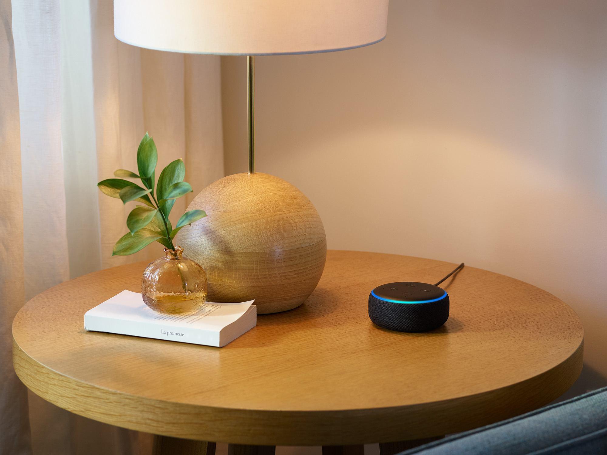Der Echo Dot steht auf einem kleinen Tisch