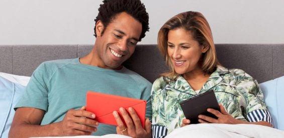 Zwei Personen schauen im Bett auf ein Amazon-Tablet