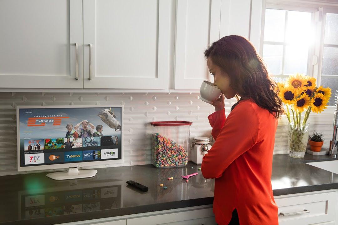 Frau steht in der Küche, trinkt Kaffee und schaut dabei auf einem Fernseher die Benutzeroberfläche des Fire TV Stick an