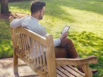 Ein Mann auf einer Parkbank mit dem neuen Amazon Kindle