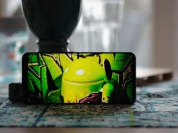 Handy mit Foto einer Android-Figur auf dem Bildschirm steht auf dem Tisch