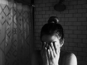 Frau sitzt ängstlich mit den Händen vor dem Gesicht in einem Badezimmer.