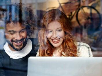 Mann und Frau sitzen lachend vor einem Notebook