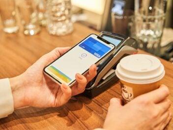 Ein iPhone X wird im Café zum Bezahlen an ein Kartenlesegeröt gehalten