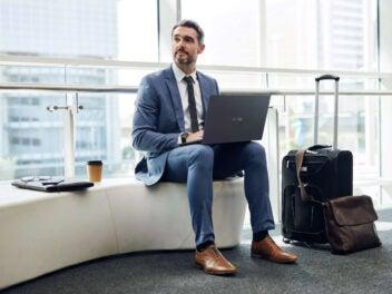 Mann mit Laptop in Lounge
