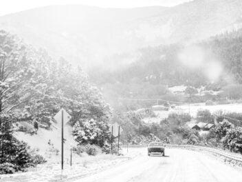 Auto fährt durch verschneite Landschaft