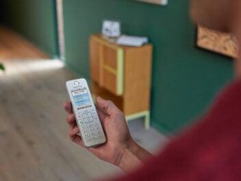 Festnetz-Telefon von AVM in der Hand eines Mannes.