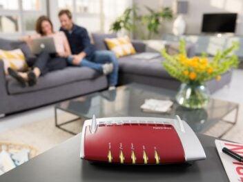 Eine FritzBox steht auf einem Tisch im Wohnzimmer, im Hintergrund surft ein Paar im Internet