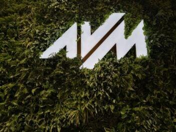Das Logo von AVM umrahmt von grünem Efeu