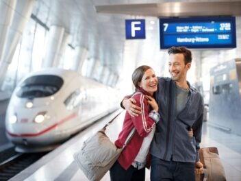 In junges Paar an einem Flughafen-Bahnhof - im Hintergrund ein ICE und die Anzeigetafel der Deutschen Bahn