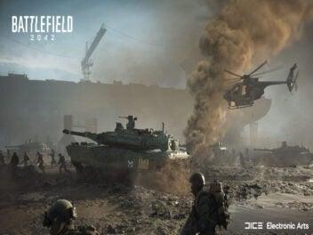 Soldaten stehen vor Panzer. Hubscharuber fliegt über dem Panzer.