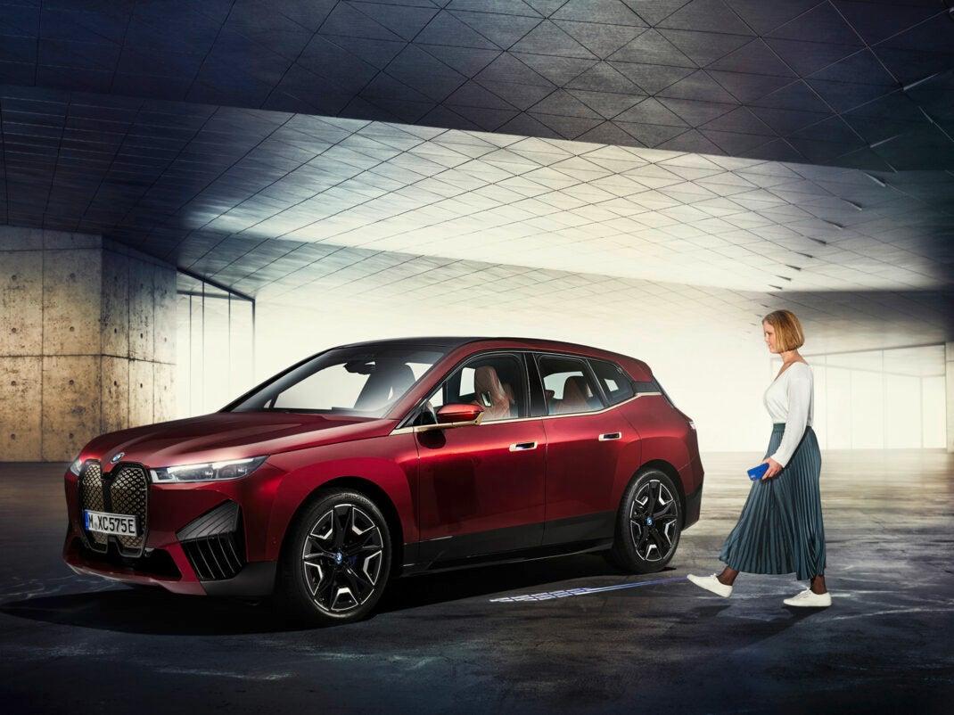 Eine Frau mit iPhone in der Hand bewegt sich zu einem BMW iX SUV.