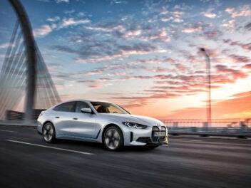 BMW i4 fährt auf einer Brücke im Sonnenaufgang
