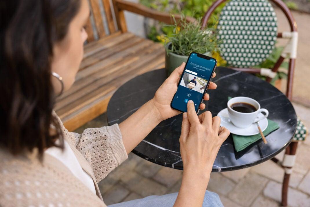 Bosch Smart Lock auf einem Handy, das eine Frau in der Hand hält.
