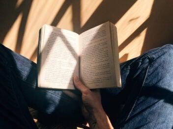 Eine Person sitzt auf einem Holzboden und hält ein geöffnetes Buch in der Hand.