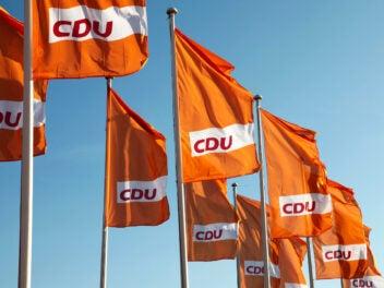 Orangene CDU-Fahnen vor blauem Himmel im Wind.