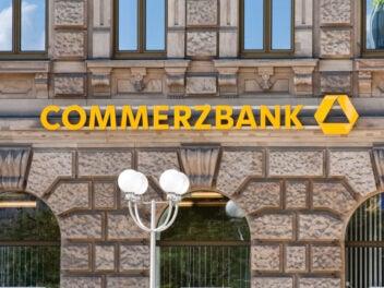 Der Commerzbank-Schriftzug an einer historischen Fassade, im Vordergrund Straßenlaternen