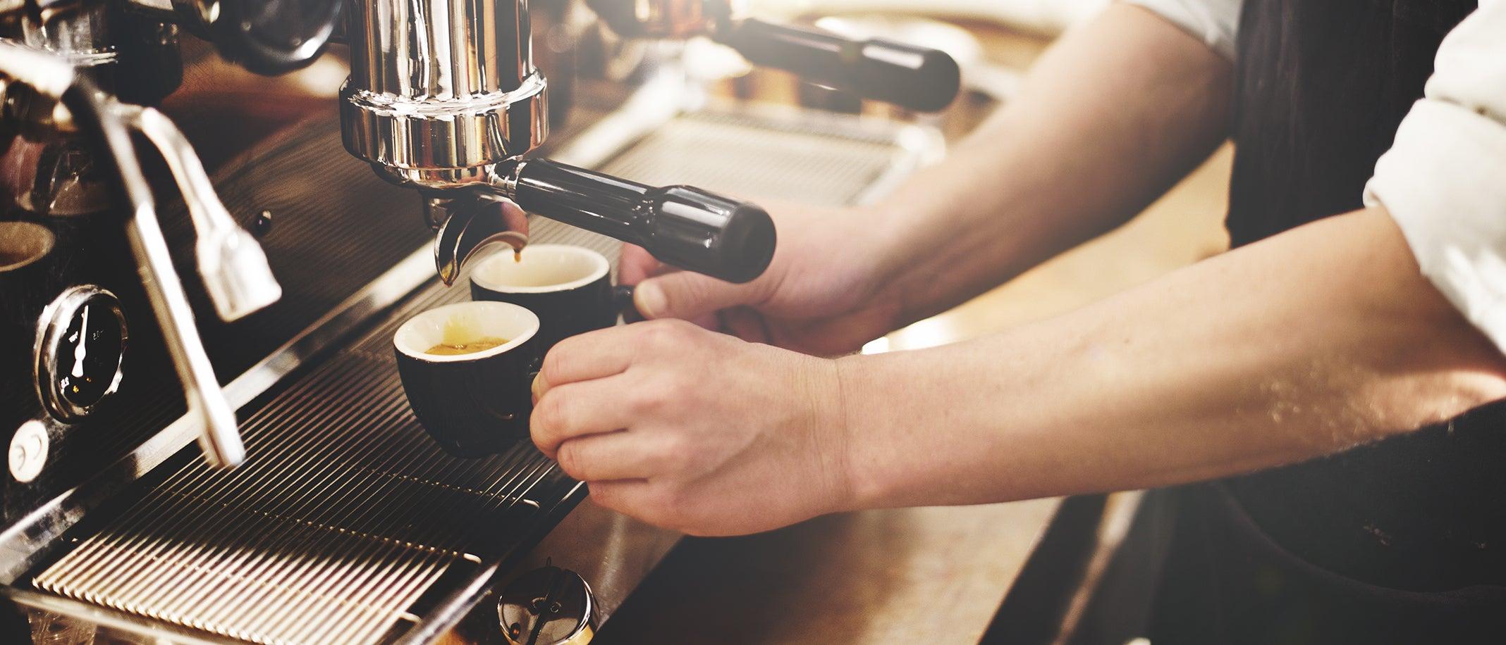 Barista bereitet zwei Espressi in einer professionellen Kaffeemaschine zu