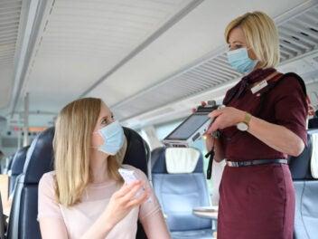 Eine Zugbegleiterin der Bahn kontrolliert das Ticket einer Frau