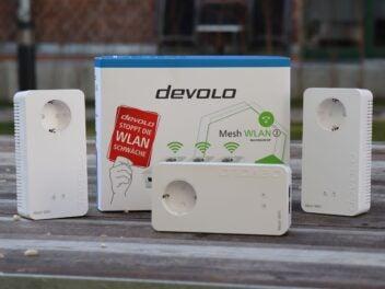 3 WLAN-Adapter stehen zusammen mit der Verpackung des devolo-Sets auf einem Holzuntergrund