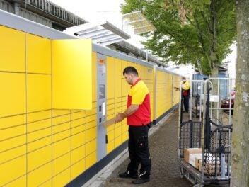 Ein DHL-Zusteller an einer Packstation