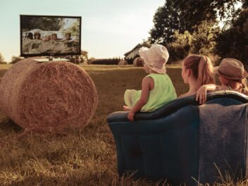 Ein Fernseher steht auf einem Strohballen auf einem Feld, eine Familie sitzt auf einer Couch davor