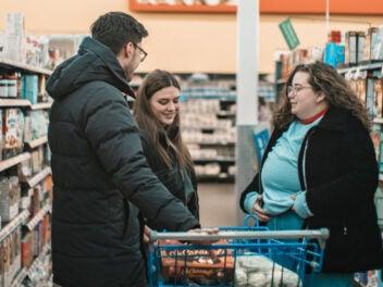 Entspannt einkaufen mit Einkaufs-Apps, so wie drei Menschen in einem Supermarkt
