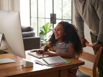 Ein Mädchen sitzt vor einem Computerbildschirm, darunter steht ein Eero-6-Router