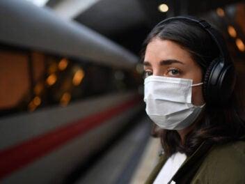 Frau steht neben einem ICE auf dem Bahngleis.