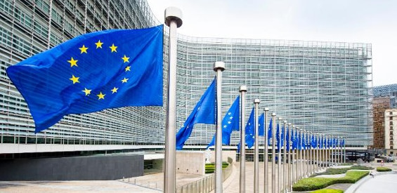Das Gebäude der EU-Kommission mit EU-Flaggen im Vordergrund
