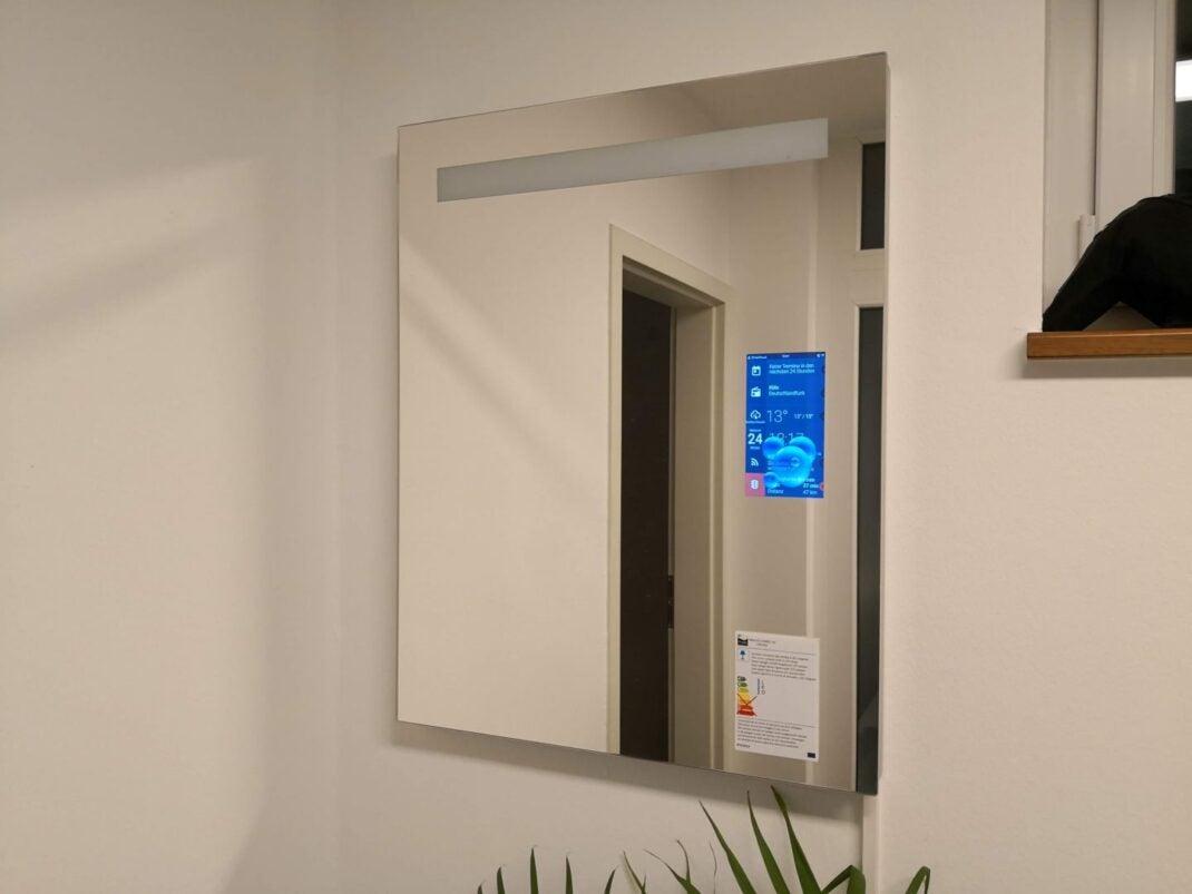 Ein Wandspiegel mit einem eingebauten kleinen Display