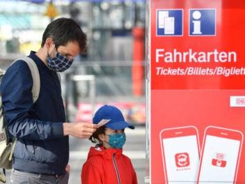 Ein Mann steht mit einem Kind an einem Ticketautomaten der Bahn