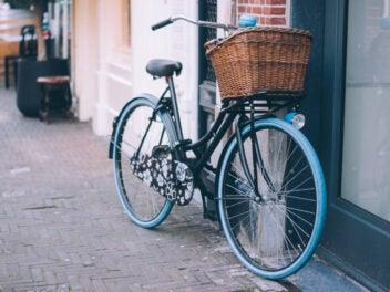 Ein Fahrrad mit blauen Reifen und braunem Körbchen steht an einer Wand.