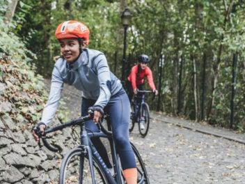 Menschen fahren mit E-Bikes in einem bewaldeten Gebiet.