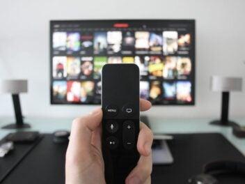 Eine Fernbedienung im Vordergrund steuert einen Fernseher im Hintergrund