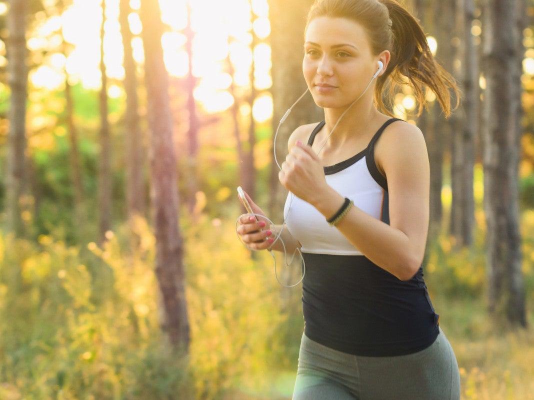 Eine Frau läuft im Wald mit dem Handy in der Hand