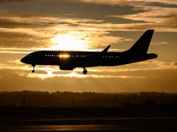 Kurzstrecken-Flugzeug landet im Sonnenuntergang.