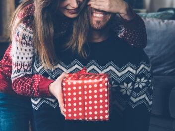 Frau beschenkt Mann zu Weihnachten