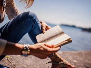 Eine Person hat ein offenes Buch in der Hand und sitzt auf einem Stein