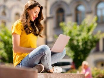 Frau arbeitet draußen mit einem Laptop