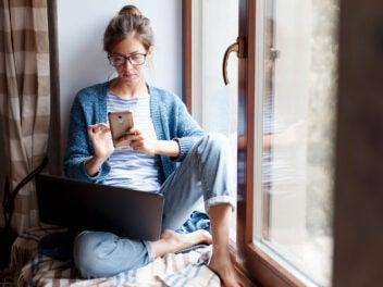 Frau sitzt mit Smartphone und Notebook am Fenster