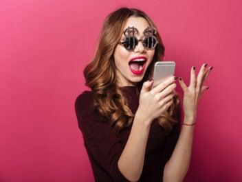 Frau mit Smartphone freut sich